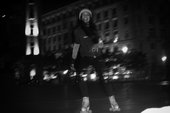 A person happily rollerskates through a city at night