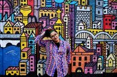 A person in a colourful patterned shirt standing against a colourful patterned wall
