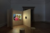 photograph of the exhibition. plywood structures small stools and a film projected onto the wall