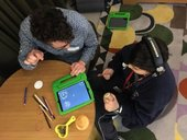 Kids sitting with a tablet at a sound art workshop