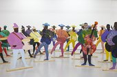 A group of 2D cut-out Black figures appear in colourful dress spaced out across a gallery