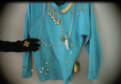 Film still of blue sweater with gold bells and ropes attached