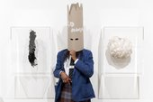 A student in a mask beside two mask artworks