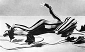 A person lays on the floor in a black and white striped costume