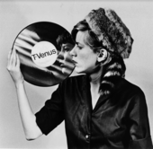 Black and white photograph of a woman looking at her reflection in a vinyl record