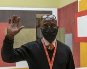a visitor assistant in a mask stands in Tate Britain foyer.