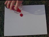 a hand over a blank paper poring a red liquid