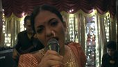 Film still of an indian woman singing into a microphone in a karaoke bar