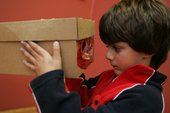 Kid looking into the sunset box he has made