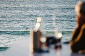 A person watches a surfer in the sea from Tate St Ives Cafe Terrace