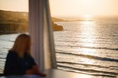 A person admires the view over Porthmeor beach at sunset from Tate St Ives' Cafe Terrace