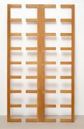 Sculpture made of pine standing upright against a wall, a wooden slatted framework