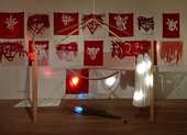Red and white flags against a white wall; a wooden construction above a wooden branch hung with clothing and beads
