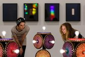 Two people looking at an installation with light bulbs in it