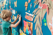 Young boy sticks a colourful drawing to a blue wall