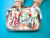 Hands in foam with marbled ink