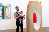 a man holding a baby in a sling looks at a big Barbara Hepworth sculpture in a gallery space
