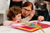 Children talk whilst holding paint brushes