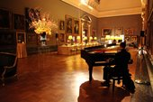 a  long table is set up for dining in a traditional gallery room, with a piano