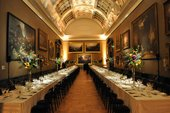 two long tables set up for dining in a traditional gallery space