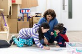 A mother and two kids draw on the floor and laugh