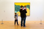 An adult and two young children looking at a painting.