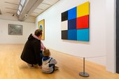 A parent and child crouch on the floor in front of an artwork. There is a wire barrier between them and the artwork.