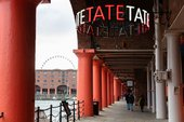 outside of Tate Liverpool on the Albert Dock, the walk way is industrial with big columns and there is a neon sign for Tate overhead.