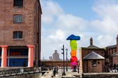 the side of Tate Liverpool, a red brick industrial building held up by large red pillars. To the right is a large sculpture made up of brightly coloured rocks stacked vertically. The sky behind is blue with white fluffy clouds.