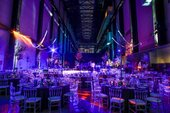 Turbine Hall set up with purple light and several tables and chairs
