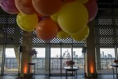 Photograph of the Level 10 Viewing Platform with orange and yellow balloons hanging from the ceiling and a view of St Pauls