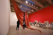 large red sail hanging from ceiling in gallery space