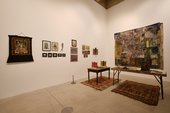 works hanging on gallery walls and a table covered in objects