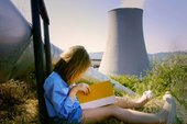 Film still from Mikhail Karikis's 'Children of Unquiet' showing a young girl reading a book in front of a power plant cooling tower
