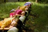 Still from Mikhail Karikis'sChildren of Unquiet film showing children lying with their eyes closed and heads resting on a pipe in the woods