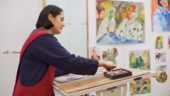 Photograph of a woman drawing with pastels and standing at an easel