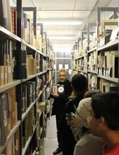 Photograph down a narrow corridor with tall archival shelving on either side; a man speaks to a group, holding up an archival item - a CD or DVD with booklet
