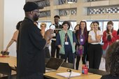 Participants on the Tate Intensive course gather round workshop leader and artist Harold Offeh