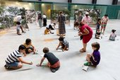 Kids sitting in a circle on the floor drawing