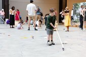 A boy draws on the floor of the Turbine Hall using a pen on a stick