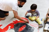 A boy and his father draw on the floor with red pens
