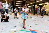 A girl stands in front of others drawing on the Turbine Hall floor