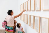 A woman points at art on the wall with her two kids looking on