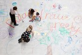 Photo of Turbine hall commission: People drawing with coloured pencils on a large white paper covered floor