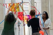 Three people building a colourful sculpture in Tate Britain