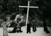 men stands next to a wooden cross on a beach