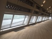 Photograph of part of the floor and windows in the Tate Exchange space at Tate Modern, empty