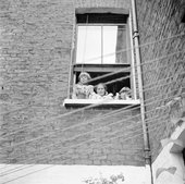Girls look down from a first floor window of a brick house, with washing lines in front of them