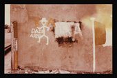 Conrad Atkinson, Colour photograph of a wall in Northern Ireland painted with a stick man, an Irish flag, and the words, 'Dads Army'