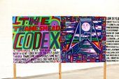 a colourful long painting stands on wooden slats the first panel says 'the thamesmead codex'